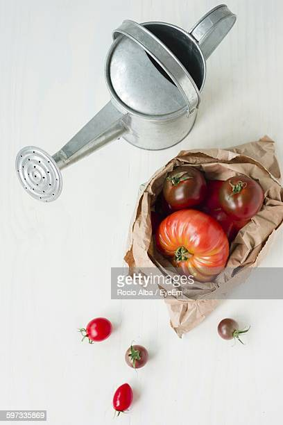 High Angle View Of Watering Can And Tomatoes On Table