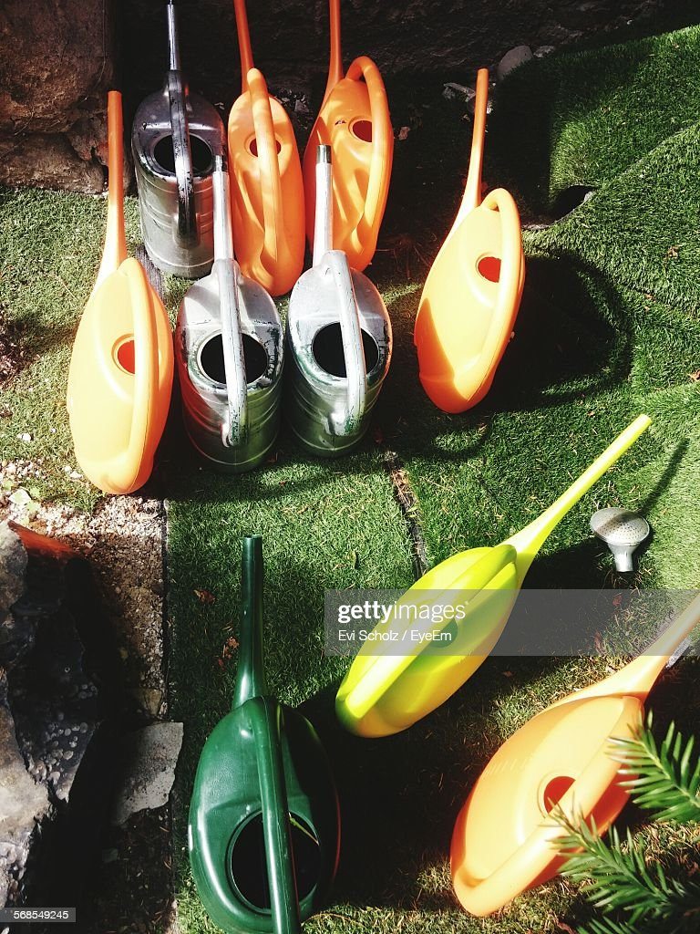 High Angle View Of Watering Cans On Field : Stock Photo