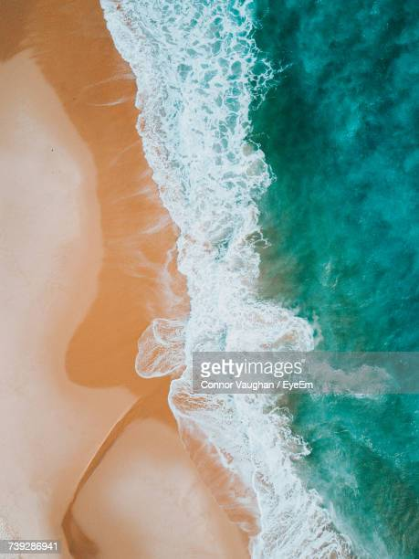 high angle view of wave on beach - tide stock pictures, royalty-free photos & images