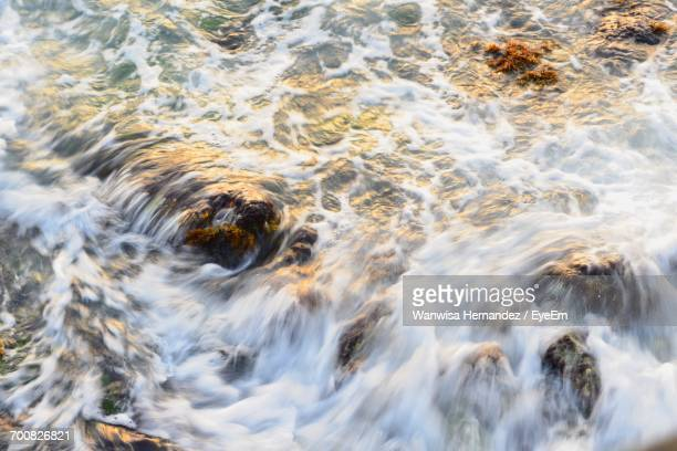 High Angle View Of Waves On Rocks In Sea