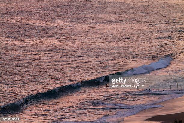 High Angle View Of Waves Reaching Towards Shore During Sunset