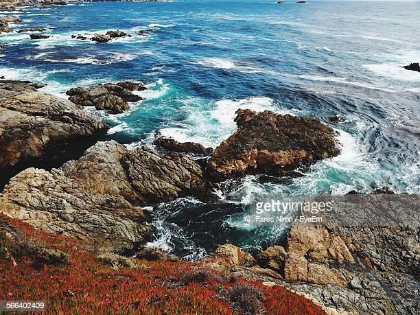 High Angle View Of Waves Splashing On Rocky Coastline