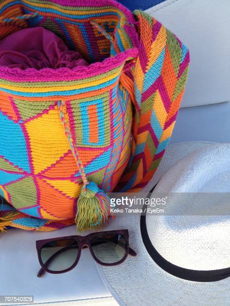 High Angle View Of Wayuu Bag And Straw Hat With Sunglasses On Table