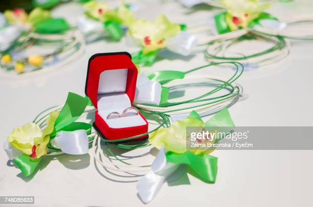 High Angle View Of Wedding Rings Amidst Artificial Flower Decoration On Car Hood