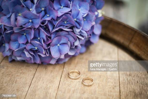 High Angle View Of Wedding Rings By Purple Flowers On Wooden Table