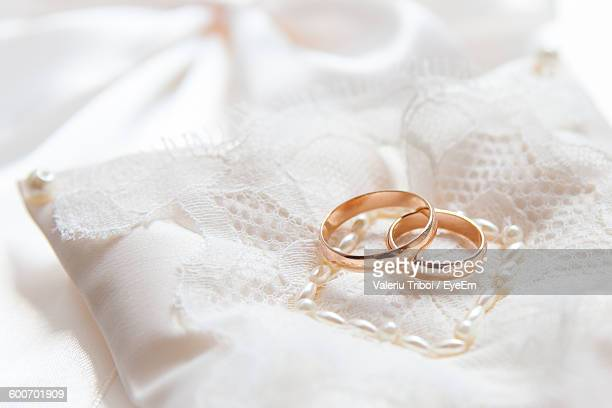 High Angle View Of Wedding Rings On Fabric At Table