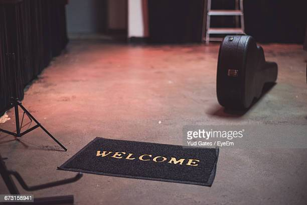 high angle view of welcome sign on doormat by guitar case on floor - guitar case stock pictures, royalty-free photos & images