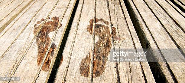 High Angle View Of Wet Footprint On Floorboard