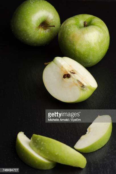 High Angle View Of Wet Granny Smith Apple Over Black Background