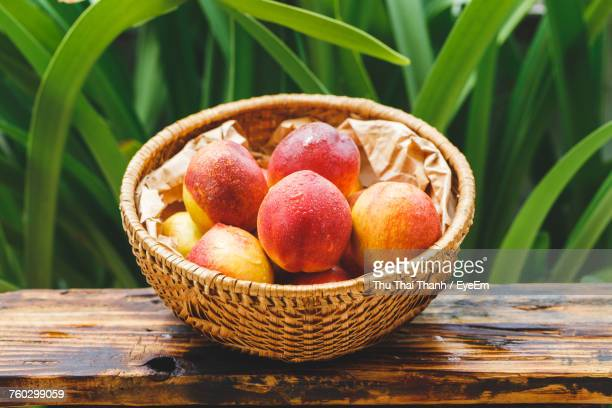 High Angle View Of Wet Peaches In Basket On Wooden Table Against Plants