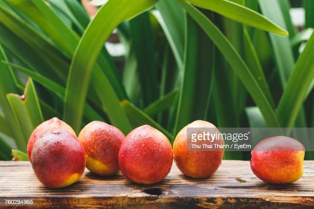 High Angle View Of Wet Peaches On Wooden Table Against Plants