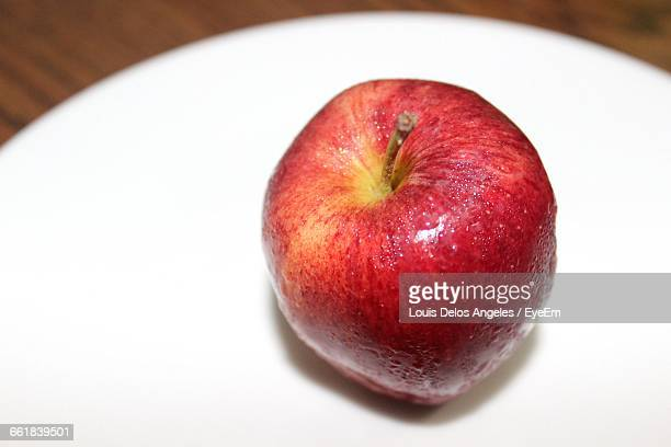 High Angle View Of Wet Red Apple In White Plate