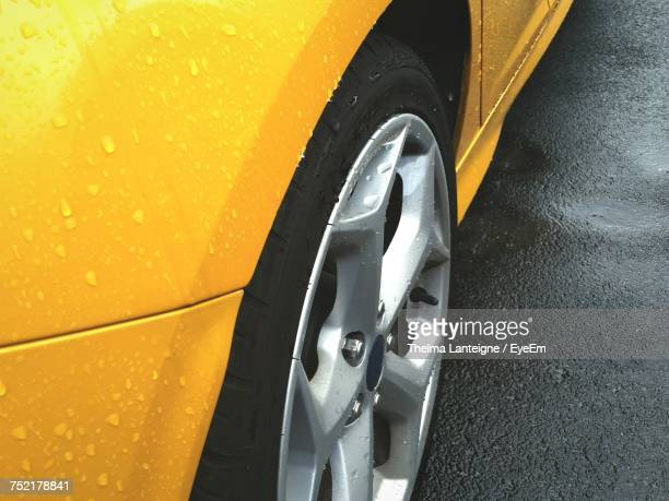 High Angle View Of Wet Yellow Car On Street