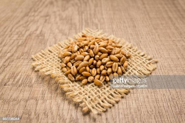 High Angle View Of Wheat On Jute Over Wooden Table