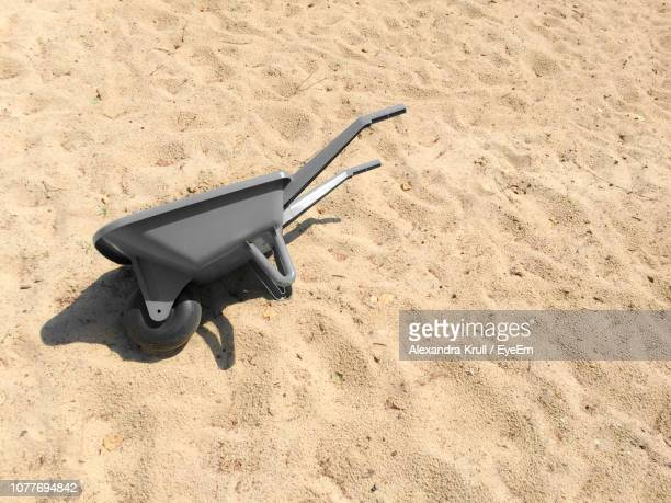 High Angle View Of Wheelbarrow On Sand At Beach