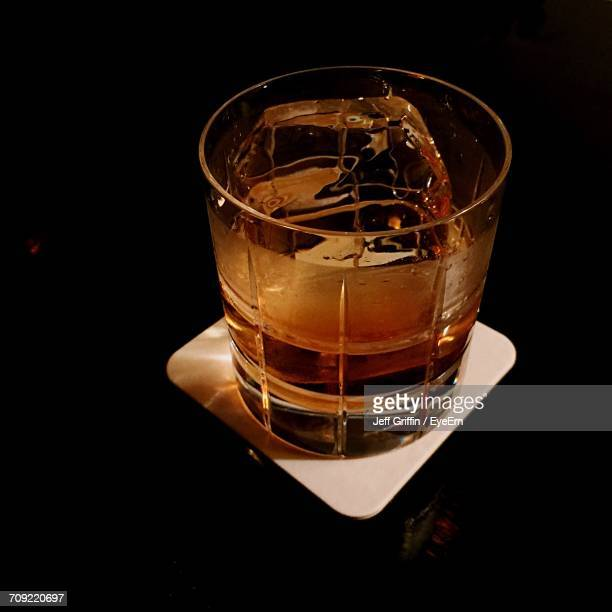 High Angle View Of Whiskey In Glass On Coaster In Darkroom
