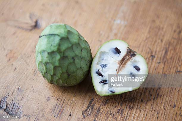 High angle view of whole and halved cherimoya on wooden table