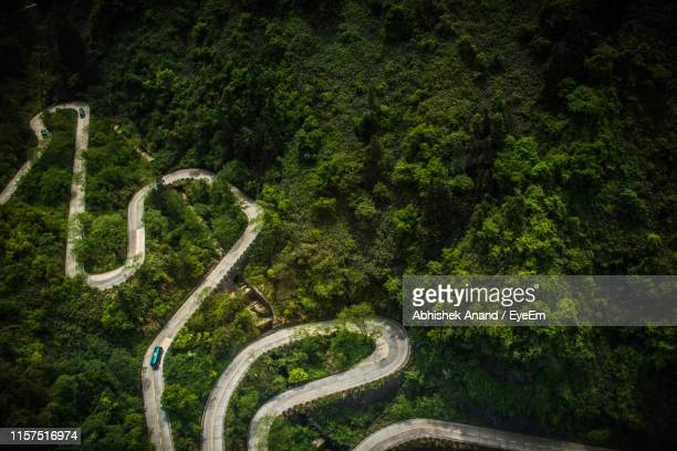 high angle view of winding road amidst trees in forest - tianmen stock pictures, royalty-free photos & images