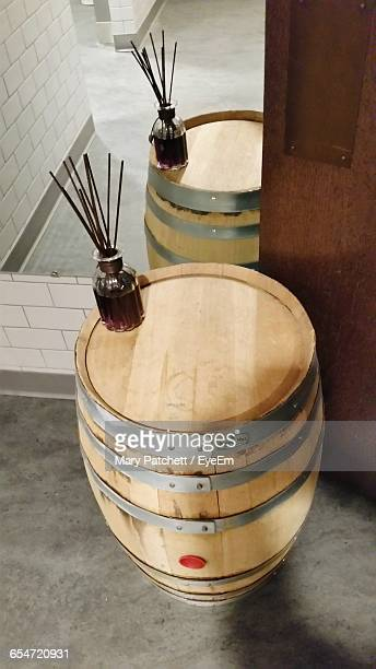 High Angle View Of Wine Bottle Drinking Straws On Cask By Mirror