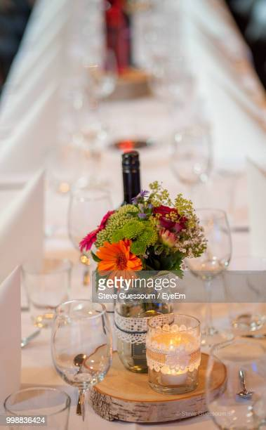 High Angle View Of Wineglasses With Flower Vase Arranged On Table