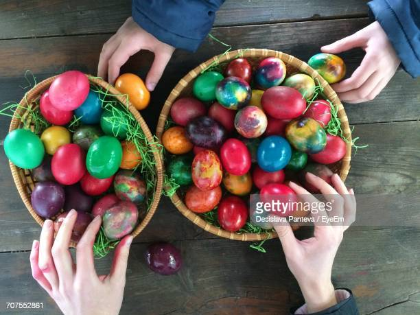 High Angle View Of Woman And Child Arranging Multi Colored Eggs