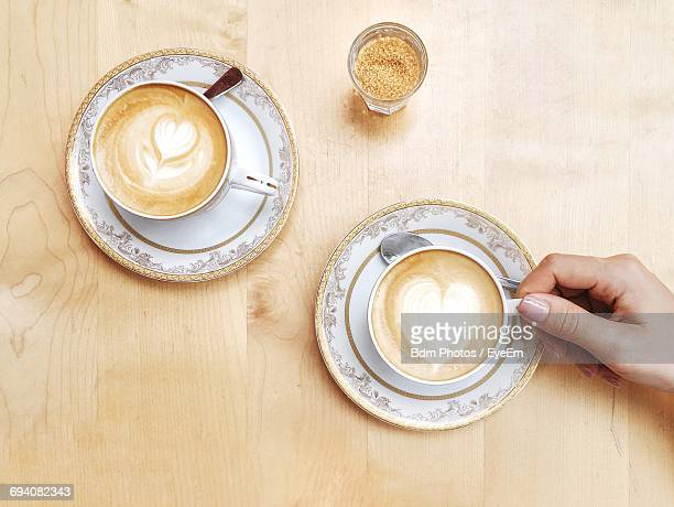 High Angle View Of Woman And Coffee Cups On Table