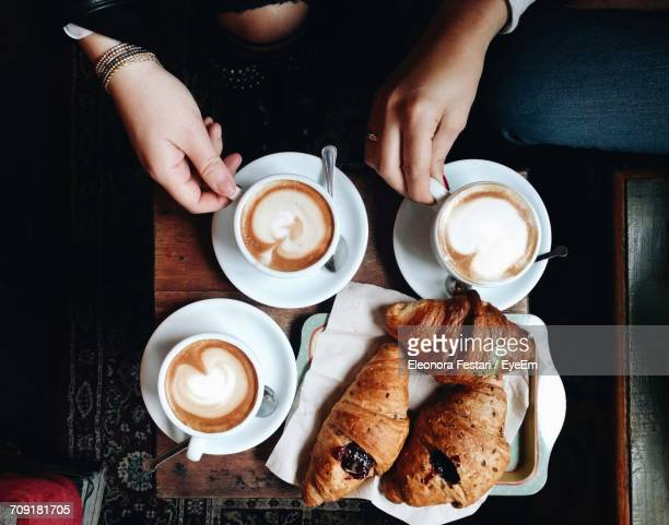 High Angle View Of Woman And Coffee On Table
