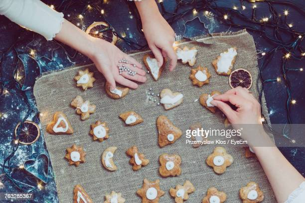 High Angle View Of Woman And Girl Preparing Cookies On Table