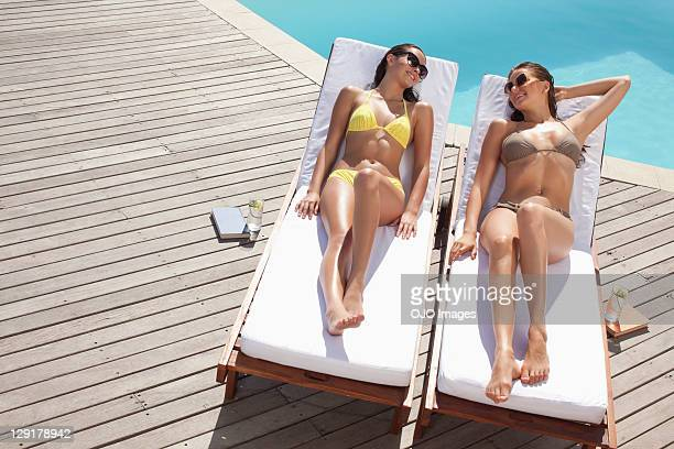 high angle view of woman and teenager lying on lounge chair - girls sunbathing stock photos and pictures