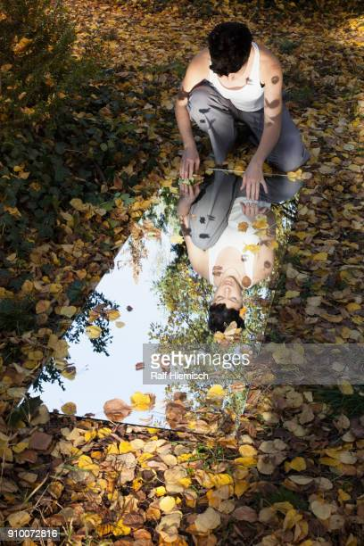 High angle view of woman and trees reflecting in mirror while sitting on dry leaves at park during a