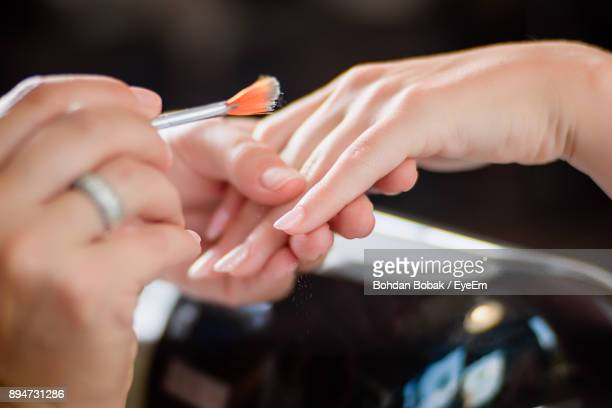 high angle view of woman applying powder on customers hand - manicure stock pictures, royalty-free photos & images