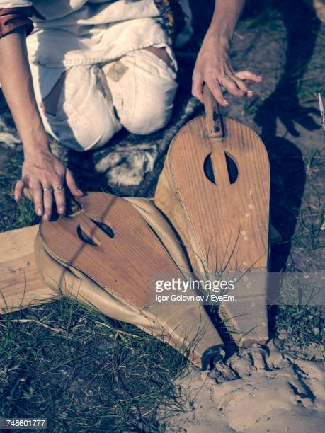 High Angle View Of Woman Blowing Fire Through Bellows On Grassy Field