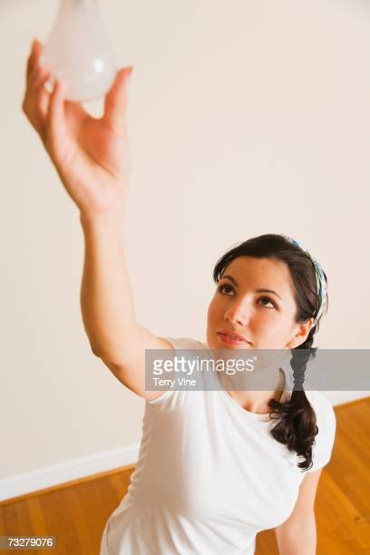 High angle view of woman changing light bulb indoors