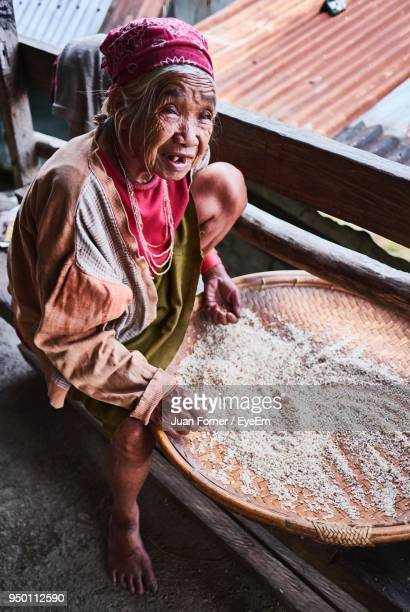 High Angle View Of Woman Cleaning Grain While Sitting On Bench