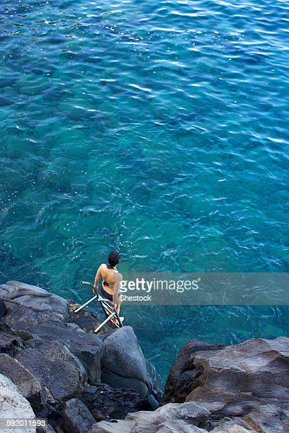 High angle view of woman climbing ladder into ocean