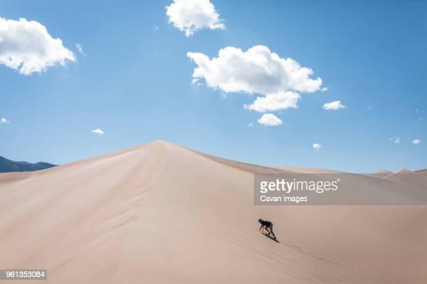 high angle view of woman climbing sand dune at national park during sunny day - great sand dunes national park stock pictures, royalty-free photos & images
