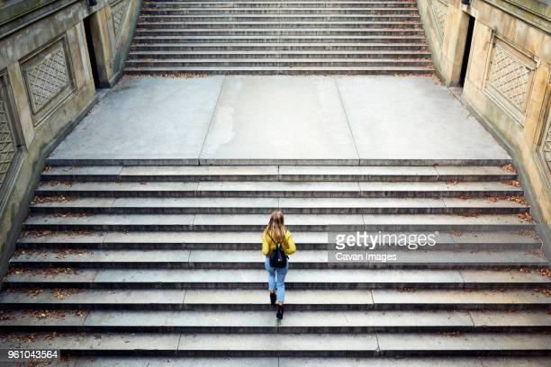 high angle view of woman climbing steps at park - moving up stock pictures, royalty-free photos & images