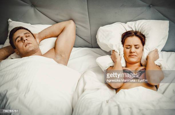 High Angle View Of Woman Covering Ears With Pillow While Man Snoring On Bed