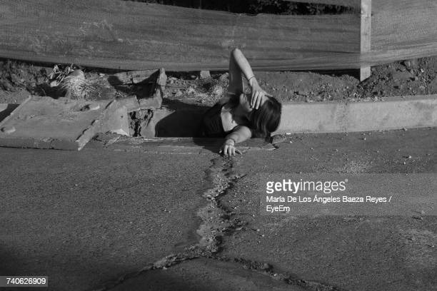 High Angle View Of Woman Covering Eyes In Gutter By Road