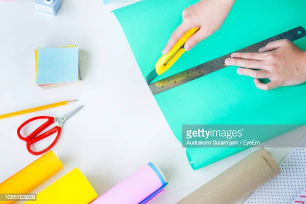 high angle view of woman cutting paper on table - basteln stock-fotos und bilder