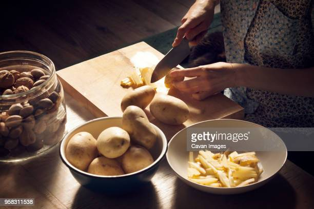 high angle view of woman cutting potatoes on cutting board at home - prepared potato stock pictures, royalty-free photos & images