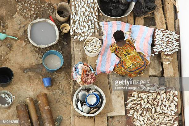 high angle view of woman drying fishes on wood - ghana stock pictures, royalty-free photos & images