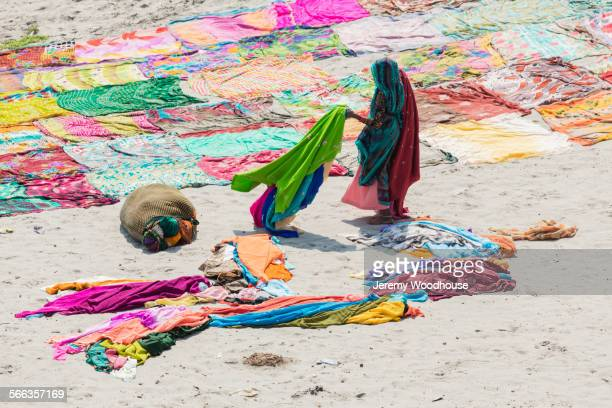 High angle view of woman drying saris on flat ground
