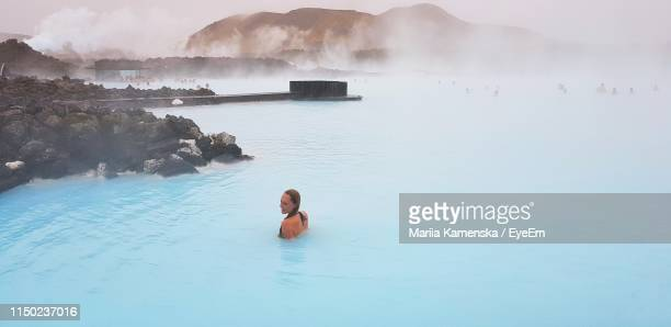 high angle view of woman enjoying in hot spring - iceland stock pictures, royalty-free photos & images