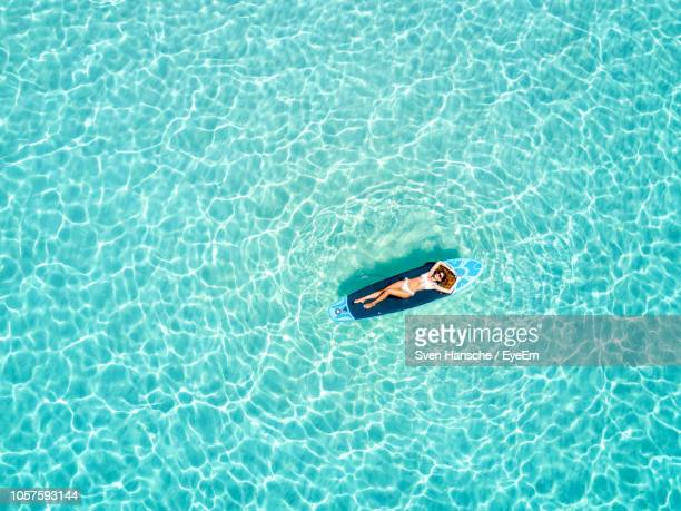 high angle view of woman floating on surfboard over sea - océan indien photos et images de collection