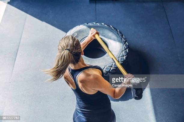 high angle view of woman hammering tire while exercising in gym - cross training stock pictures, royalty-free photos & images