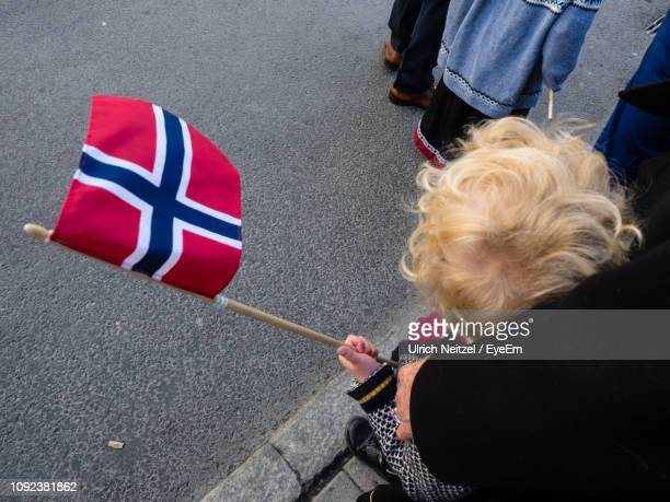 high angle view of woman holding child with flag while standing on road - norwegian flag stock pictures, royalty-free photos & images