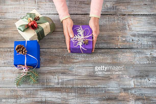 High Angle View Of Woman Holding Christmas Gift On Wooden Table