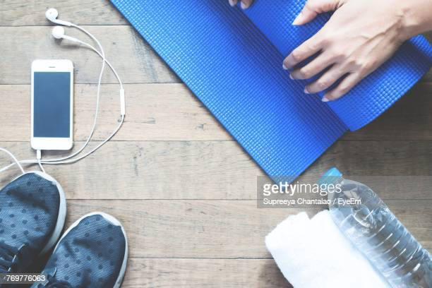 High Angle View Of Woman Holding Exercise Mat On Table