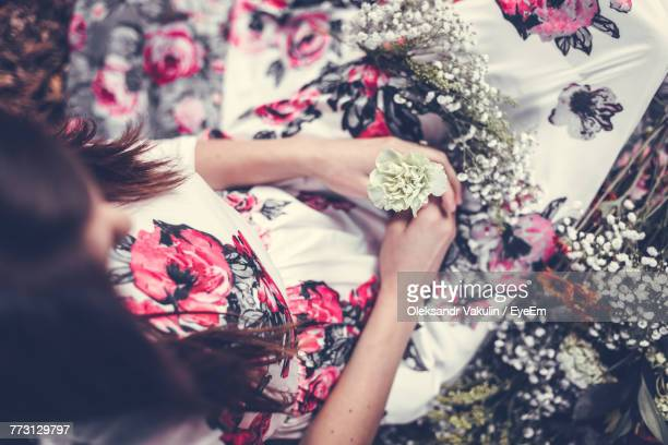 high angle view of woman holding flower - oleksandr vakulin stock pictures, royalty-free photos & images